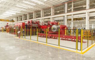 This image shows the interior of National Material of Mexico's Monterrey location, angle of the Red Bud slitter – a vibrant red steel slitter within a very large brightly lit bay within the steel plant.