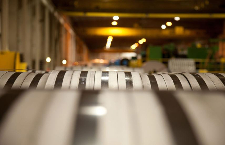 Closeup angle of slit steel coils inside of a steel plant with the large warehouse in the background.