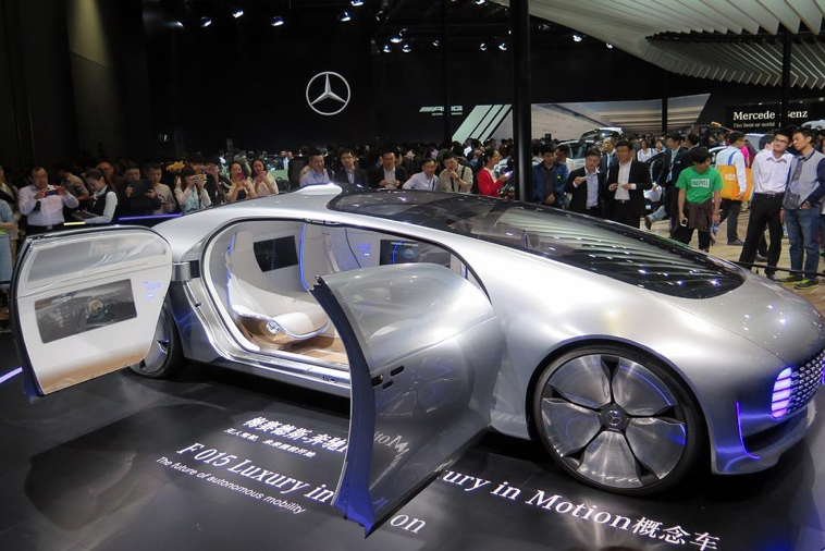 Alt Tag: The Mercedes Forward 015 concept car, a sleek, silver, vehicle draws the attention of a crowd eager for a glimpse of the futuristic self-driving car in a showroom that displays the Mercedes-Benz logo in the background.