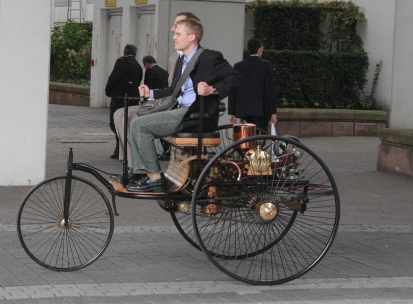 Two young men, one with his hand on the crank, ride a replica of the Benz Patent Motor Car, a three-wheeled vehicle with large back wheels and a bench for two riders.