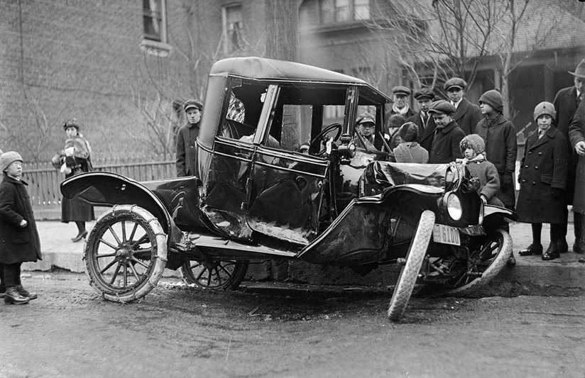 Curious onlookers stand around a wrecked car whose front wheels have been twisted and whose front end has been crushed by an impact.