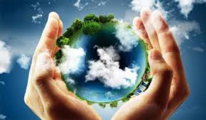 A picture of the Earth with ocean and white clouds and green trees circling it; there is a pair of pale-skinned hands cradling the globe, as if to protect it; the background is blue with white clouds.