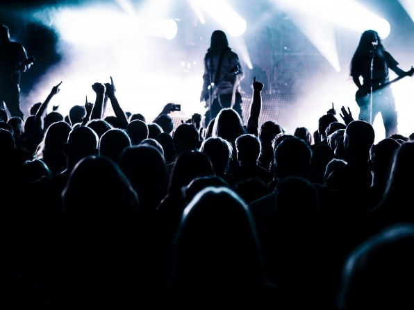 The dark silhouettes of the back of heads and some raised arms as a crowd of people look towards a brightly lit stage where multiple spotlights point in different directions showing the dark silhouette of two long-haired figures playing guitars.