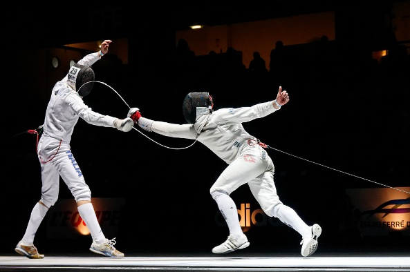 In front of a black background in which can be seen the silhouettes of a few audience members, two fencers dressed in white protective clothing and black fencing masks execute fencing offensive and defensive moves; the one on the right lunges forward with his or her right armed completely outstretched and her sword bends upward upon contacting the neck area of the opponent, and the one on the left stands straight with legs apart, left hand in the air and the right stretched forward with the sword, which is bent downward upon contact with the opponent's neck.