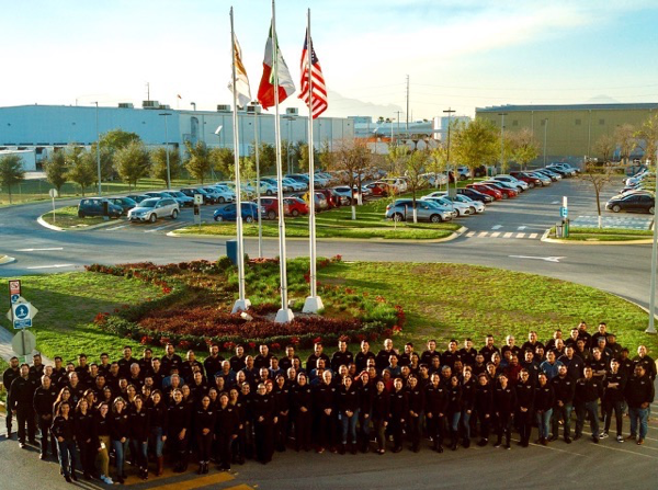 Approximately 100 National Material of Mexico employees pose outside NMM's steel processing plant on a beautiful sunny day after a company-wide celebration for receiving IATF16949:2016 certification.