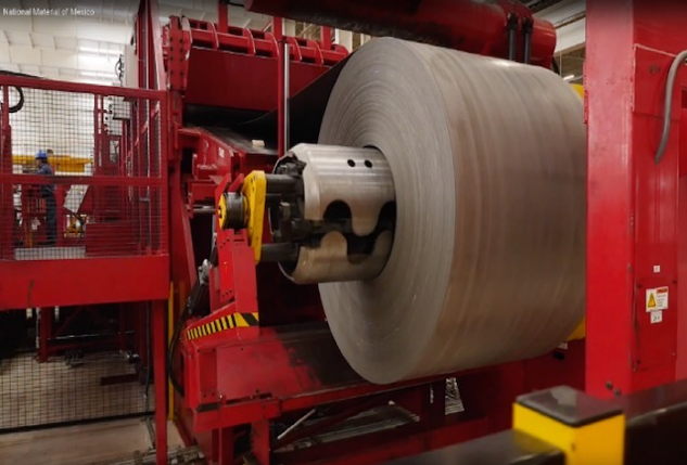 The slitter recoiler system, with a large roll of metal wound around a huge metallic cylinder, which is part of a red machine.