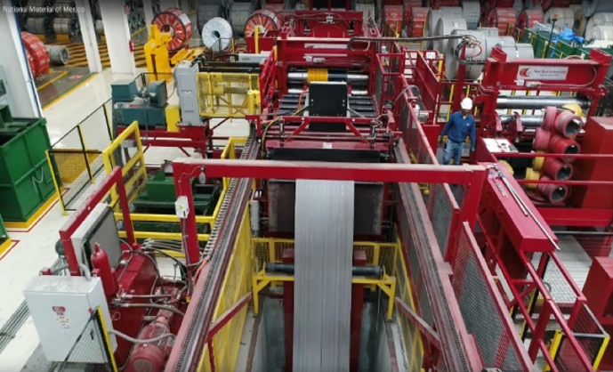 A panoramic view of the Red Bud Slitting machine, with an uncoiled length of metal going down the slitting shaft, the red structure of the slitter extending around the factory floor, a workman in white hat and dressed in blue, and a rolls of steel waiting to be slitted.