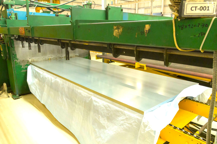 A close angle of the cut-to-length line in National Material of Mexico's brightly lit steel processing center in Monterey, Mexico.
