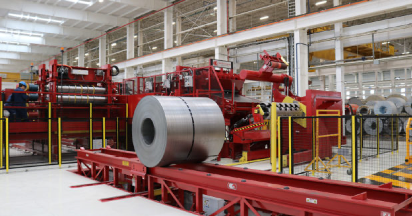 In a large, bright, ample warehouse with white floors and white columns, a long, extensive machine painted red and yellow with stairs running up to raised platforms for operating, and all around it can be seen coils of circular metal covered in red and white foil.