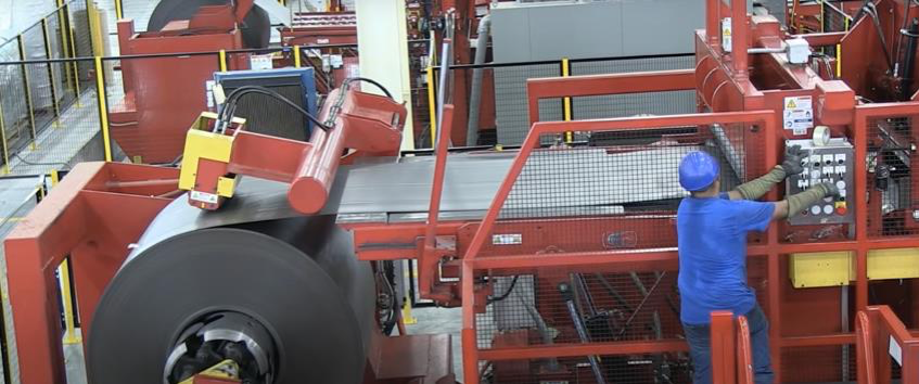 A large metal coil in the process of being uncoiled or recoiled into or out of a large conveyer belt, part of a slitting machine painted red and yellow and operated by a man in a blue shirt and a blue hardhat pushing buttons on a control panel.