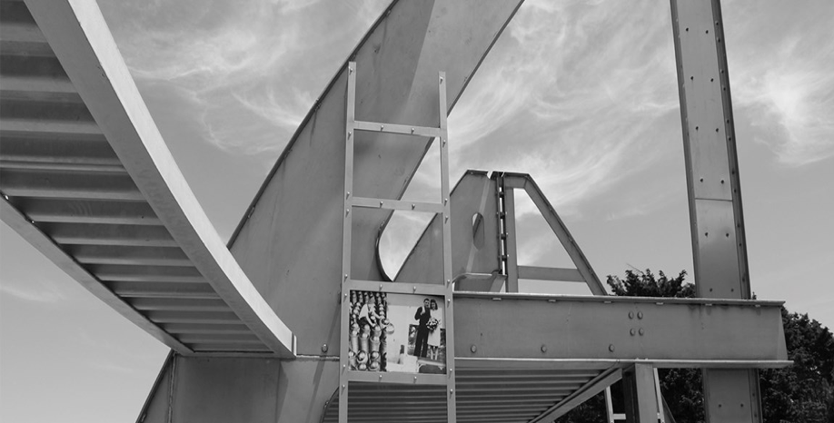 "A black and white picture showing a monument called ""Rosie the Riveter"" in front of wispy clouds; the monument consists of steel parts — one that looks like a ladder, another that looks like a walkway, and another triangular, rounded structure that could form the support piece of a bridge, all centered around a small photograph portraying three people."