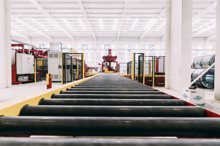 Inside National Material of Mexico's large, bright warehouse, a close, artistic shot of the rollers on the Red Bud slitting line.