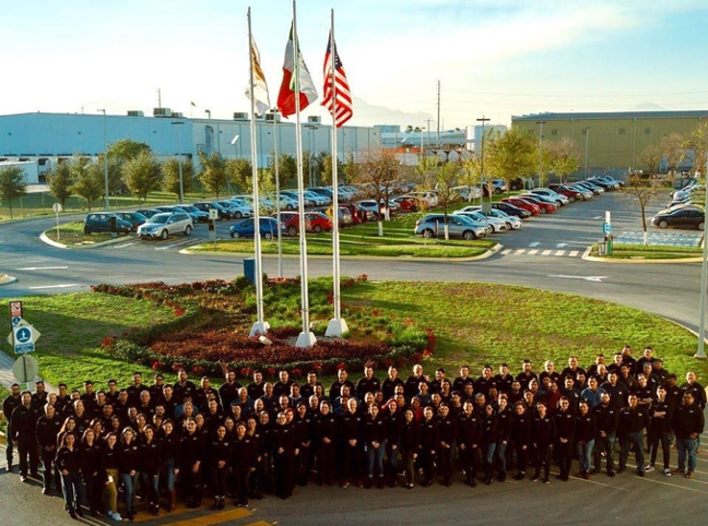 National Material of Mexico's Monterrey employees standing proudly outside their steel processing plant on a sunny day, with the Mexican flag, American flag, and the NMM flag behind them.