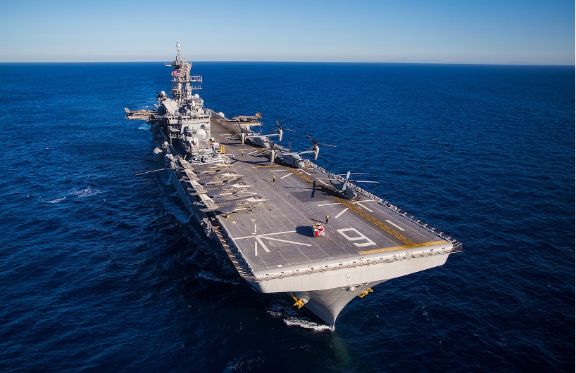 A beautiful aerial view of a military aircraft carrier in a deep blue ocean on a clear, sunny day.