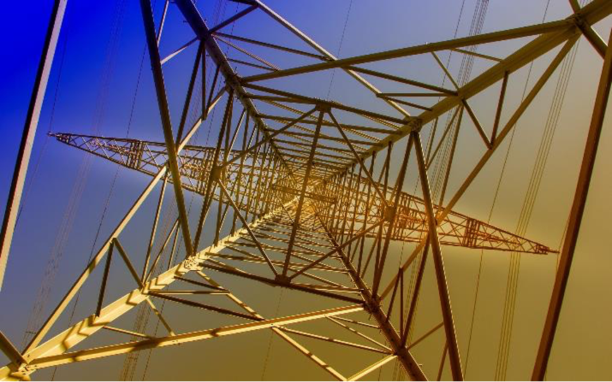 A photo looking straight up into the skeletal column of a steel tower supporting power lines.