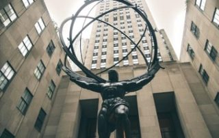 In the courtyard of a skyscraper is a statue of a muscular and bare-chested Atlas holding up the globe, represented by four concentric circles, which can also represent steel's contribution as the backbone to the world.